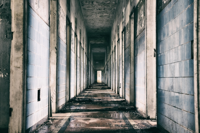 Long grey hallway of a dilapidated old asylum.