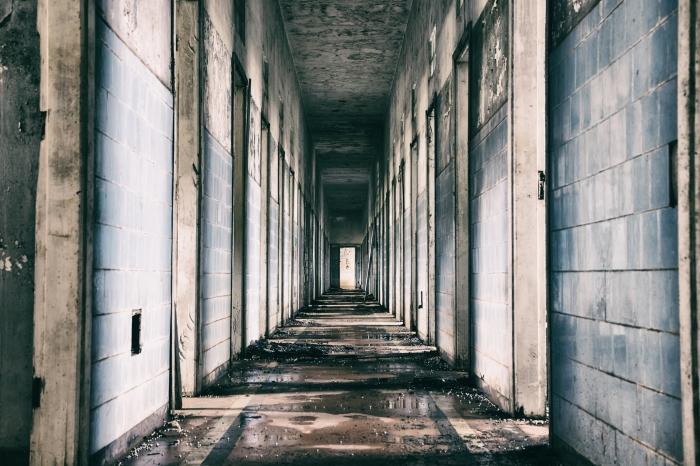 Long grey hallway of a dilapidated old asylum.